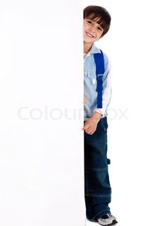 Young kid standing behind the board on white isolated background