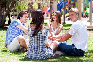 Young smiling couples sitting together playing game and having fun at the park