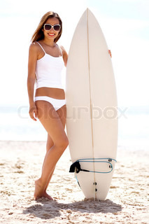 sexy woman at the Beach with surfboard in her white bikini and a surfboard at beach