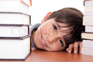 Happy young school boy surrounded by books on white background