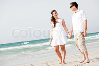 full length image of Young couple holding hands and walking on the beach