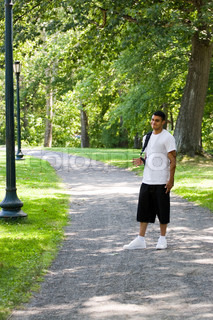 A young man walking on campus with his backpack and a positive attitude