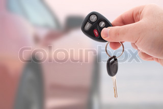 A hand holding car keys and a remote control for keyless entry