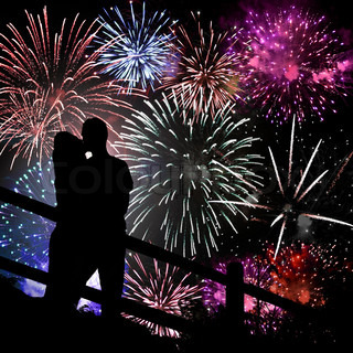 A silhouette of a kissing couple in front of a huge fireworks display
