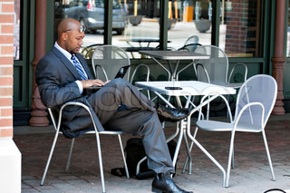 An African American business man in his early 30s using his laptop or netbook computer while seated at a cafe table outdoors