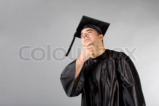 A recent college or high school graduate in his cap and gown thinking and looking contemplative