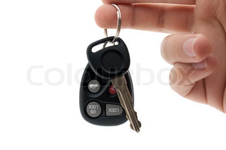 A hand holding car keys and a remote control for keyless entry isolated over white