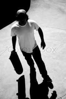 Silhouette of a skateboarder standing inside the pool at the skate park with strong contrast and dramatic shadows