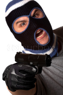 An angry looking man wearing a ski mask pointing a black handgun at the viewer Shallow depth of field with sharpest focus on the gun