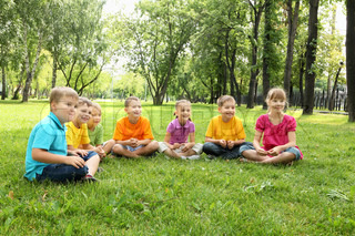 Group of children sitting together on teh grass in the park