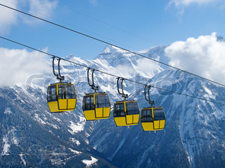 Group of bright yellow cable car cabines in swiss alps