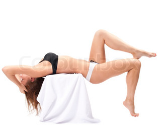 Sexy nude body of a pretty young female lying down on the support over white