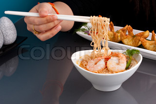 A person eating shrimp and Thai noodles from a bowl with chopsticks along with other appetizer foods