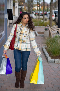 A young Indian woman carrying colorful bags out shopping in the city