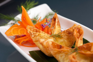 Fried thai crab cream cheese wontons or rangoons appetizer presented on a platter with fancy carrot and herb garnish