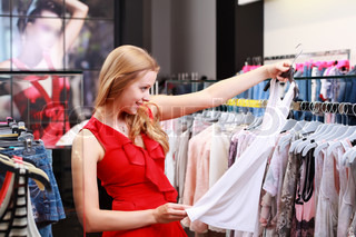 Beautiful young girl at the store chooses to purchase clothing