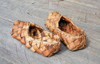 Old russian sandals made of bark on wooden floor