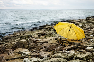concept,cold sea and gray stones focus point on yellow umbrella