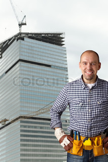 construction concept with modern building on the background, selective focus on face