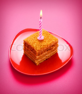 birthday cake with candle on pink background