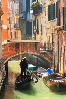 Vertical oriented image of gondola passing on small canal among old historic houses and bridge in Venice, Italy