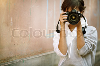 female photographer with professional SLR camera, natural light, selective focuson nearest part of lens with blend