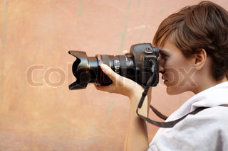 female photographer with professional SLR camera, natural light, selective focus on eye
