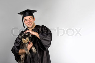 A recent college or high school graduate in his cap and gown holding his pet dog in his arms