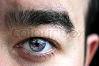 Closeup of a mans eye and eyebrow with the earth superimposed in his iris