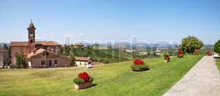 Panoramic view on green lawn, old church and hills of Piedmont in northern Italy