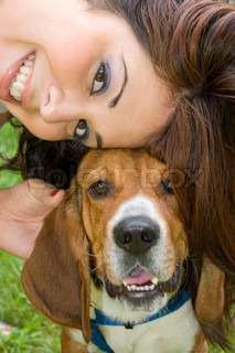 A pretty girl posing with her beagle dog - they both seem to be smiling