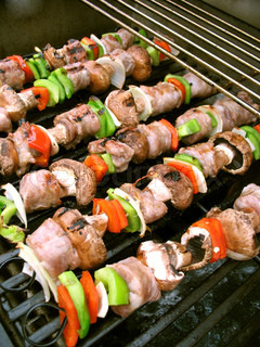 Sausage shish kebabs on skewers, cooking on the grill