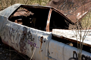 An old abandoned car body that is covered in graffiti