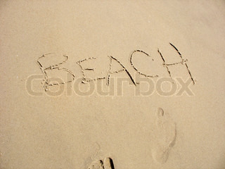 The word BEACH written in the sand along with a few footprints