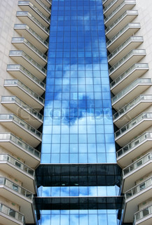 Perspective of tall modern building with sky reflection