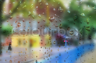 heavy rain drops on window with colour background