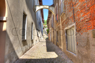 Narrow paved street among vintage brick houses in town of Avigliana, northern Italy