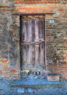 Vertical oriented image of vintage wooden door and brick wall in Roddi - small town in Piedmont, northern Italy