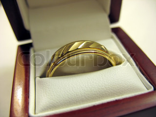 A yellow gold mens wedding band inside its box