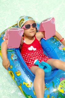 Young child is relaxing in boat in swimming pool