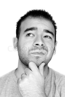 A young man with his hand on his chin thinking an important decision - black and white