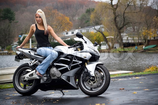 A pretty blonde girl posing on a motorcycle