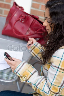 An attractive Indian woman texting or searching the web on her cell phone while seated at a table outdoors