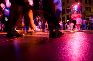 A low shot of the dance floor with people dancing under the colorful lights