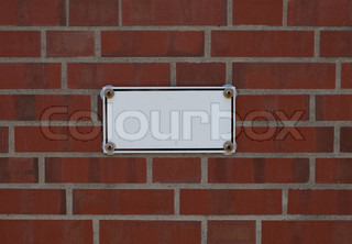 white metal plate with bolts on brick wall background