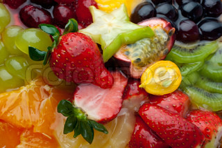 Macro of mixed fruits and berries in gel (raspberry, strawberry, red and white grapes, kiwi, clementines, pineapple, passionfruit, carambola)