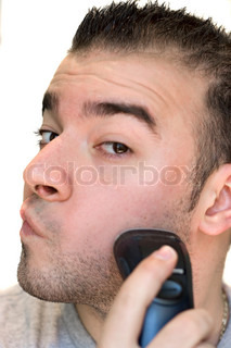 A closeup of a young man shaving his beard off with an electric shaver