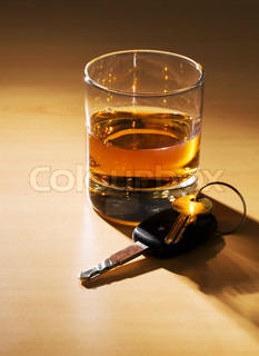 Car keys and a glass of alcohol on a table