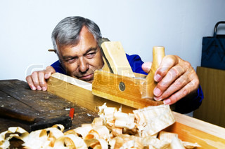 A carpenter with a planer and wood shavings in the workshop