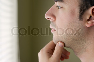 A young man with his hand on his chin thinking an important decision